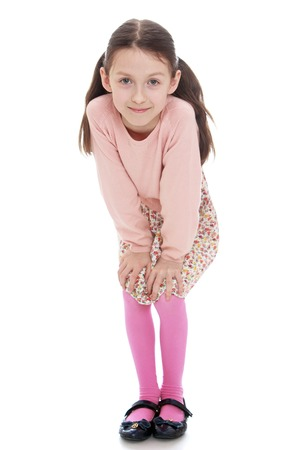 liked: Cheerful girl in a dress and pink cardigan liked put his hands on his knees - isolated on white background