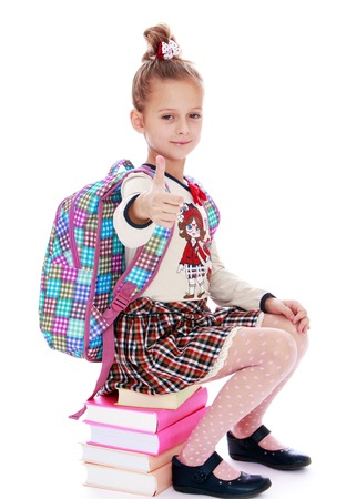 elegantly: Serious, elegantly dressed schoolgirl sitting on a stack of books putting forward a hand with a raised thumb, the gesture all right hitchhiking - isolated on white background