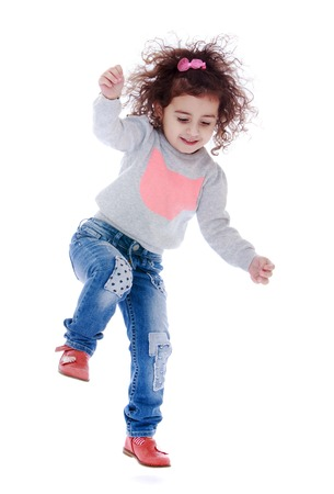 Fun little curly girl fun jumps - isolated on white background