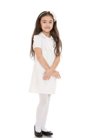white stockings: girl in a stylish fashion white short dress and white stockings stands with folded hands in front of him - isolated on white background