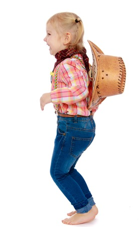 barefoot cowboy: Happy little blonde girl in cowboy clothes , jeans and hat, jumping, barefoot, turning to the camera sideways - isolated on white background Stock Photo