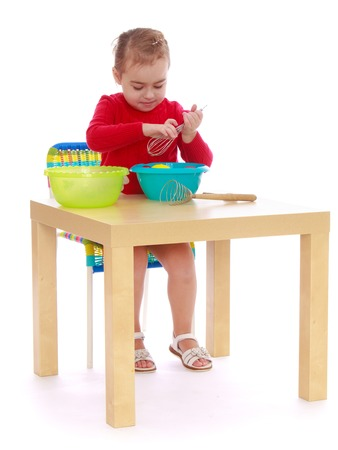 montessori: The girl in the Montessori kindergarten is sitting at the table playing with plastic utensils - isolated on white background