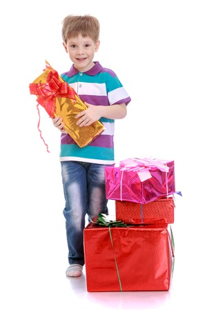 beautifully wrapped: Smiling blond boy in a striped t-shirt and jeans holding a beautifully wrapped gift tied with a bow - isolated on white background