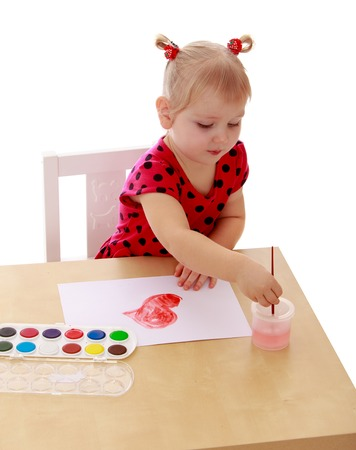 abbassa: The little blonde girl in a red summer dress polka dot lowers the brush with water, girl paints with watercolors sitting at the table - isolated on white background