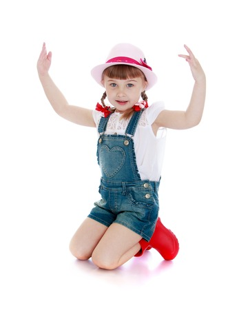 bangs: Beautiful little hairy girl with short bangs and braids in which the braided bows on his knees in the hat, denim overalls and red boots - isolated on white background