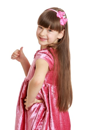velvet dress: Beautiful girl with long, lush hair and short bangs in pink velvet dress shows the gesture of thumb is all right , or hitchhiking , close-up - isolated on white background