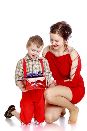 red shorts: Happy little boy in a plaid shirt and a long bright red shorts holding a box of Packed red wrapping paper, next to the boy and leaned his mom she is very happy - isolated on white background