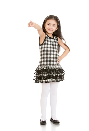 barely: Fashionable little girl with long dark hair in a short plaid dress with white stockings shows index finger to the side, the girl smiles she barely mouth a few teeth- isolated on white background Stock Photo