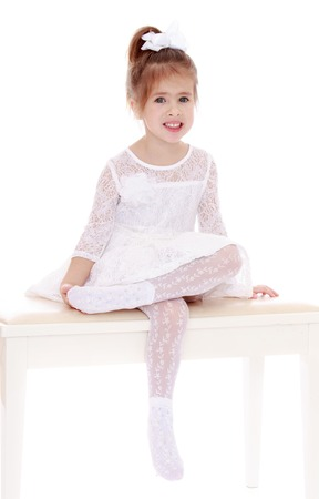 pulled over: Delicate little blonde girl with her hair pulled up into a bun in translucent white short lace dress-white lace tights on a white wooden bench put one leg over the other