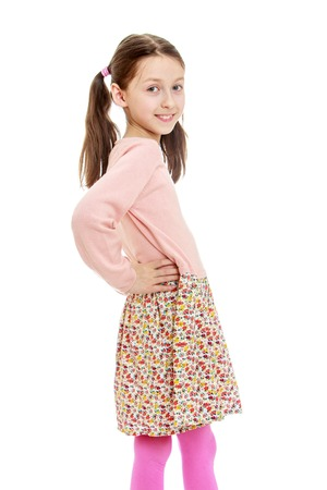 infant school: Funny, provocative very skinny little girl with long dark hair braided in a ponytail , in a long cotton dress posing turning to the camera sideways , close-up- isolated on white background Stock Photo