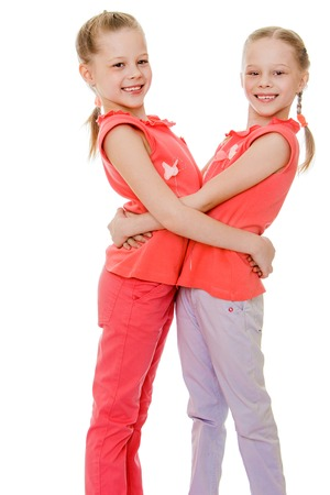 niñas gemelas: Adorable niñas gemelas divertido sonriente mirando a la cámara, la chica es buena para estar juntos siempre feliz con cada-otro aislado en blanco Foto de archivo