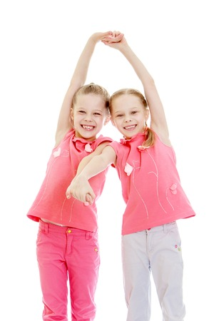 ni�as gemelas: Adorable twin girls fun held hands and laughing into the camera, close-up-Isolated on white Foto de archivo