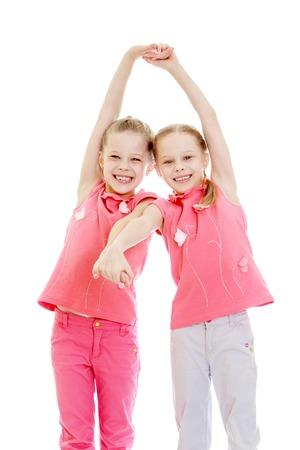 niñas gemelas: niñas gemelas diversión adorable tomado de las manos y riendo en la cámara, primer plano, aislado en blanco