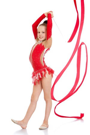 bathing suits: Very slender and beautiful young girl in a red bathing suits embroidered sequined perform exercises with the tape , the girl is engaged in gymnastics , she prepares to compete-Isolated on white Stock Photo