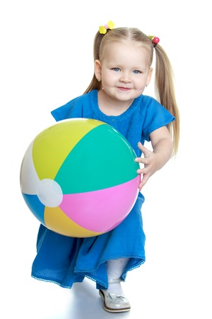 one little girl: Adorable little chubby blonde girl in a blue summer dress holding a large inflatable striped ball-Isolated on white Stock Photo