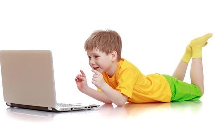 bermudas: Hermoso niño de pelo rubio en una camisa amarilla, pantalones cortos verdes que mienten en el suelo y presiona el botón de la computadora portátil, aislado-alfabetización equipo chico maravilla en blanco Foto de archivo