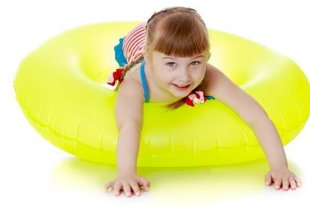 petite fille avec robe: La petite fille blonde aux longues tresses sur la t�te, dans un maillot de bain ray� se trouve sur le grand cercle pour nager dans la mer et le fleuve, la fille se repose avec les parents en vacances � la mer Banque d'images