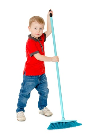 industrious: Very industrious little boy in red shirt and jeans sweeping the floor with a big brush , he loves to help parents with the housework hes trying very hard-Isolated on white Stock Photo