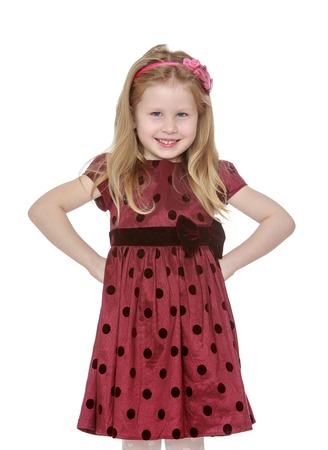 girl in burgundy dress: Smiling Caucasian girl with long hair which keeps the headband in Burgundy polka dot dress stands in front of the camera, hands on hips , close-up-Isolated on white