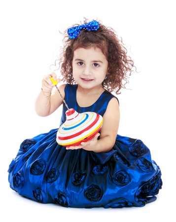 velvet dress: Cute little curly-haired girl in Sinop velvet dress sitting on the floor and holding a spinning top-Isolated on white