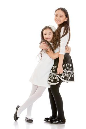 twee modieuze, mooie meisjes zusters plezier knuffelen elkaar-Geïsoleerd op wit