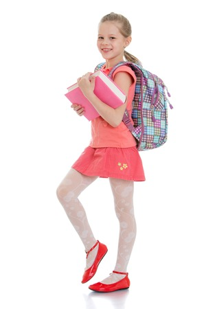 uniforms: Cute blonde girl schoolgirl in red skirt and red shirt is holding a thick book behind the girls hanging school backpack-Isolated on white background