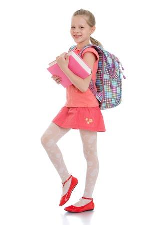školačka: Roztomilá blondýnka školačka v červené sukni a červené košili drží tlustou knihu za dívkami visí školní batoh, izolovaných na bílém pozadí Reklamní fotografie