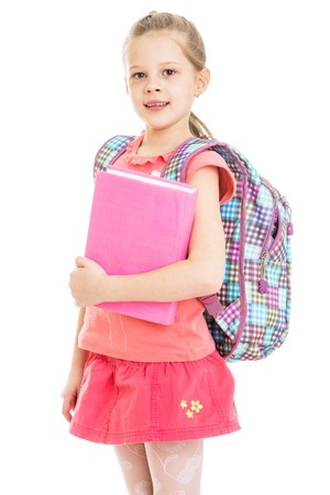school uniform: Cute blonde girl schoolgirl in red skirt and red shirt is holding a thick book behind the girls hanging school backpack-Isolated on white background