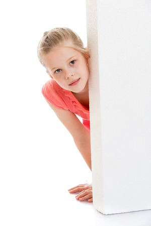 Encantadora chica rubia se asomó por detrás de obstáculos, aislado sobre fondo blanco Foto de archivo