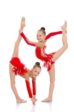 gymnastik: Zwei Schwestern, die Turnerinnen arbeiten zusammen, um durchzuführen schöne gymnastische Übung-Isoliert auf weißem Hintergrund Lizenzfreie Bilder