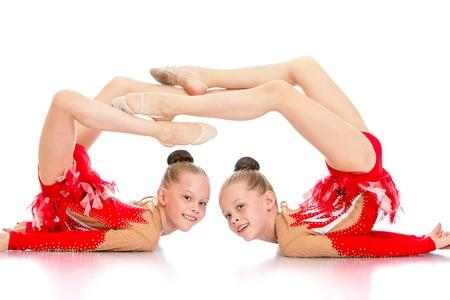 gimnasia ritmica: Dos hermanas gimnastas juntos tirado en el suelo realizando un hermoso ejercicio de gimnasia aislada en el fondo blanco
