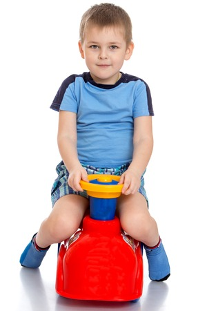 spins: Beautiful fair-haired little boy riding a plastic bike , he spins the wheel-Isolated on white background