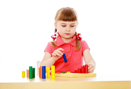 montessori: Beautiful little girl in a Montessori class, sitting at the table playing an educational game-Isolated on white background