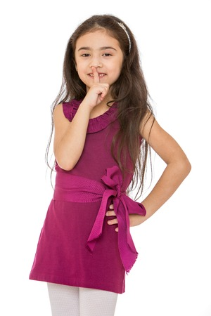 finger bow: Beautiful dark-haired little fashionable girl in a short Burgundy dress tied with a bow put a finger to her lips , close-up-Isolated on white background Stock Photo