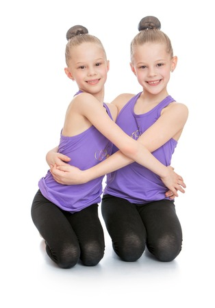 Two charming blonde sisters with tightly braided hair into a ball in sports clothes sitting on your lap and cuddling-Isolated on white background