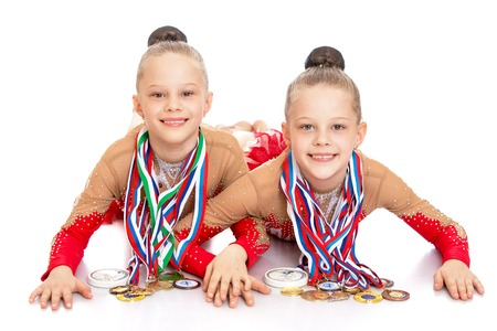 gimnasia ritmica: Dos gimnastas niñas encantadoras en ropa deportiva se encuentran en el suelo y demuestran las medallas ganadas en las competiciones. Las medallas colgadas al cuello una gran cantidad de ellos.-Aislado en el fondo blanco