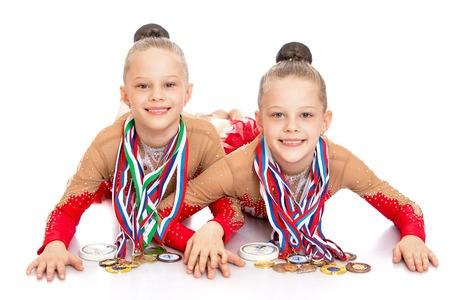 gymnastik: Zwei charmante Mädchen Turnerinnen in Sportkleidung auf dem Boden liegen und zeigen die Medaillen bei Wettbewerben. Die Medaillen hängen um den Hals eine Menge them.-Isoliert auf weißem Hintergrund