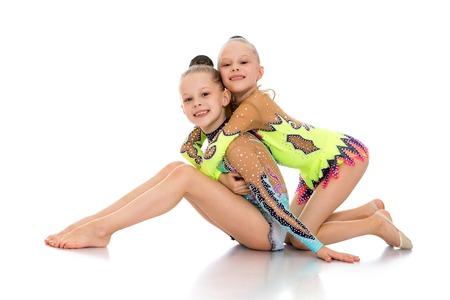 turnanzug: Lustige Mädchen schönen Athleten in Sportgymnastikanzüge sitzen auf dem Boden und hug-Isoliert auf weißem Hintergrund Lizenzfreie Bilder