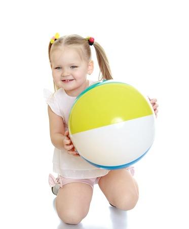 beach ball girl: Blanco ni�a adorable con el pelo trenzado en trenzas est� de rodillas y sosteniendo delante de una gran bola de playa con rayas, muchacha empujones a los padres en la orilla del mar resort.-Aislado en el fondo blanco