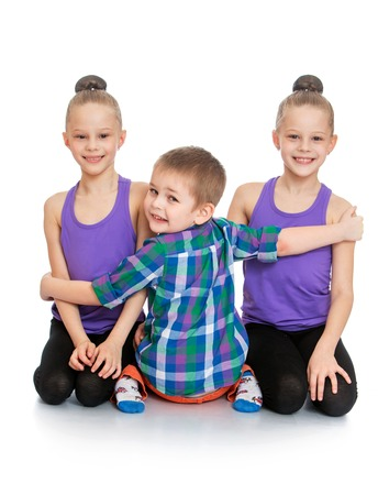 girl lying studio: two girls sisters in t-shirts and sports jerseys tights sat on his knees on the floor,hugging the boys younger brother who sits in the chamber with his back turned his head , only three people-Isolated on white background Stock Photo