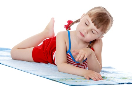 Beautiful little girl with short blond bangs and long braids which are plaited red bows in a short red skirt lies on a soft Mat lifting up feet , the girl rests with parents and relatives at a seaside resort , she tans in the sun , girl taking sun bath-Is