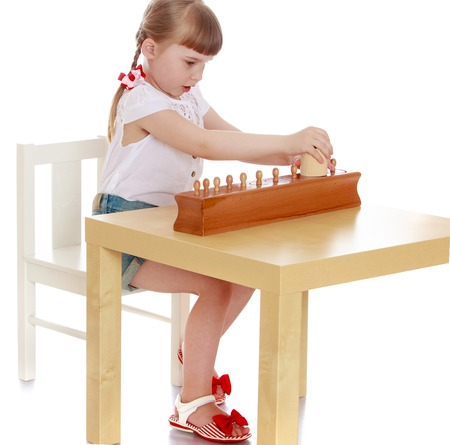 Schattig meisje aan tafel zitten en studeren Montessori materialen, Montessori kleuterschool Stockfoto