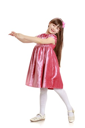 velvet dress: Adorable little long-haired girl in a long velvet dress and white stockings stretched out her arms , the girl enters into the image it is engaged in a theatrical Studio-Isolated on white background