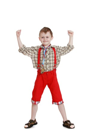 red shorts: Cheerful little boy in a long red shorts is widely spreading legs raised in the upper arms with clenched fists , the boy shows his biceps-Isolated on white background