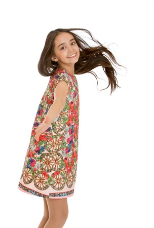 dark haired: Beautiful dark haired teen girl Oriental appearance in a short colorful dress whirls around, close-up-Isolated on white background