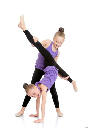Two girls gymnasts in purple shirts and black athletic tights doing sport exercises