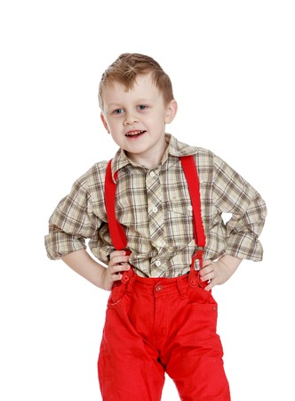 red shorts: Funny little boy in a plaid shirt and red shorts with straps, close-up-Isolated on white background Stock Photo