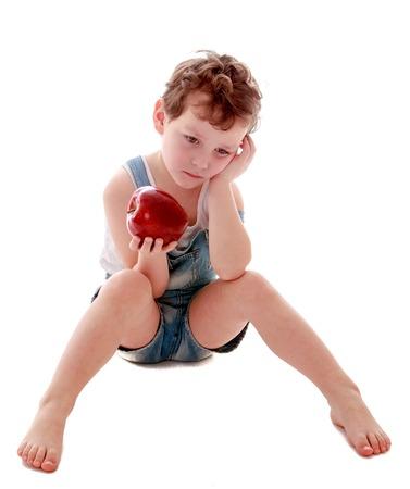 niño parado: Niño pequeño triste en pantalones cortos de mezclilla cortos sentado en el suelo con los pies descalzos y aspecto triste celebración de una gran manzana jugosa roja Foto de archivo