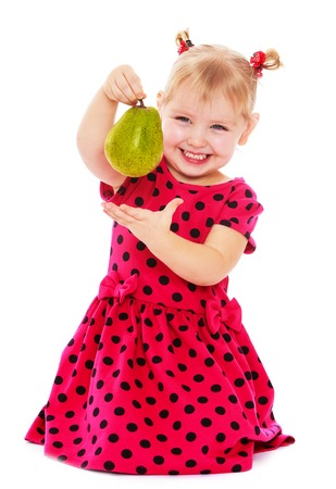 Cute little blonde girl in a red dress with polka dots sitting on the floor and holding in outstretched arms of ripe pear