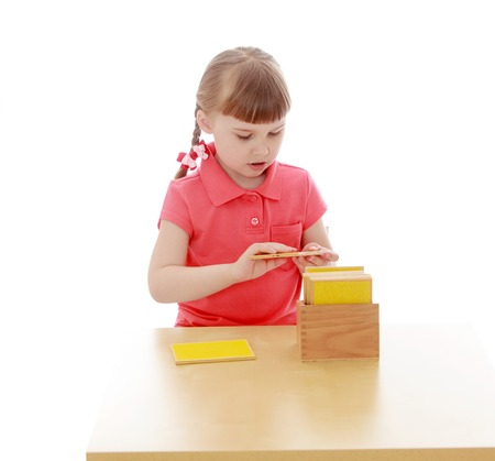 keen: Keen little girl blonde short bangs and braids in which the braided ribbons in red shirt sitting at the table and examines Montessori material
